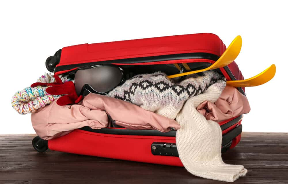 Photo of a Stuffed Suitcase. Click Here for a Handy Ski Trip Packing List.